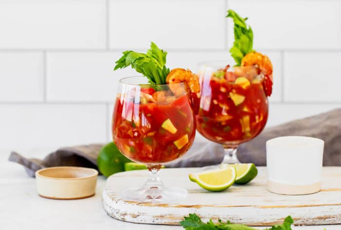 a white cutting board with two stemmed glasses of an appetizer made with tomato juice, lime, and shrimp