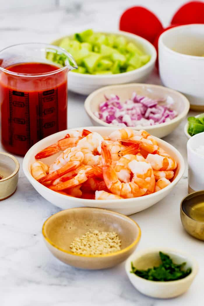 ingredients for shrimp cocktail, including shrimp, diced avocado and red onion, and tomato juice