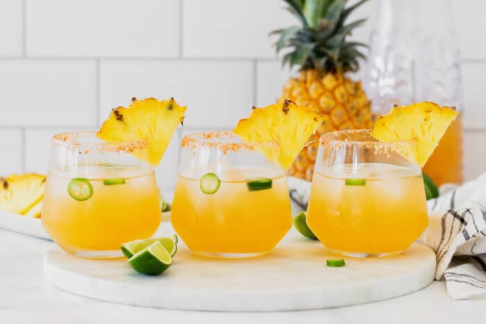 3 glasses of pineapple jalapeno margaritas, arranged in a straight row