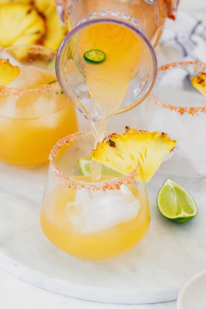 pouring pineapple jalapeno margarita mixture from a pitcher to a glass