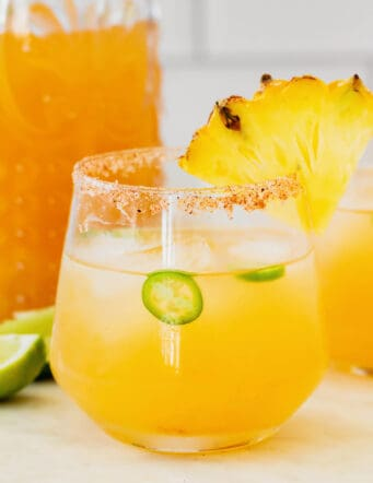 a pineapple jalapeno margarita in a glass rimmed with chili salt