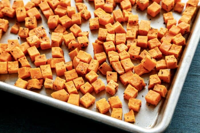 roasted cubes of sweet potatoes on a rimmed metal sheet pan
