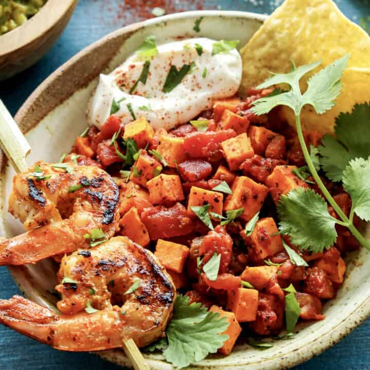 a pottery bowl with a skewer of grilled shrimp and diced sweet potatoes and tomatoes