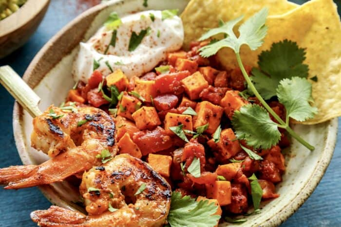 a pottery bowl of diced sweet potatoes and tomatoes, plus a small skewer of grilled shrimp
