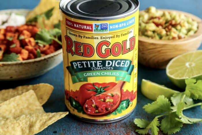 a can of Red Gold Petite Diced Tomatoes with Green Chilies, plus a bowl of guacamole and a grilled shrimp bowl in the background
