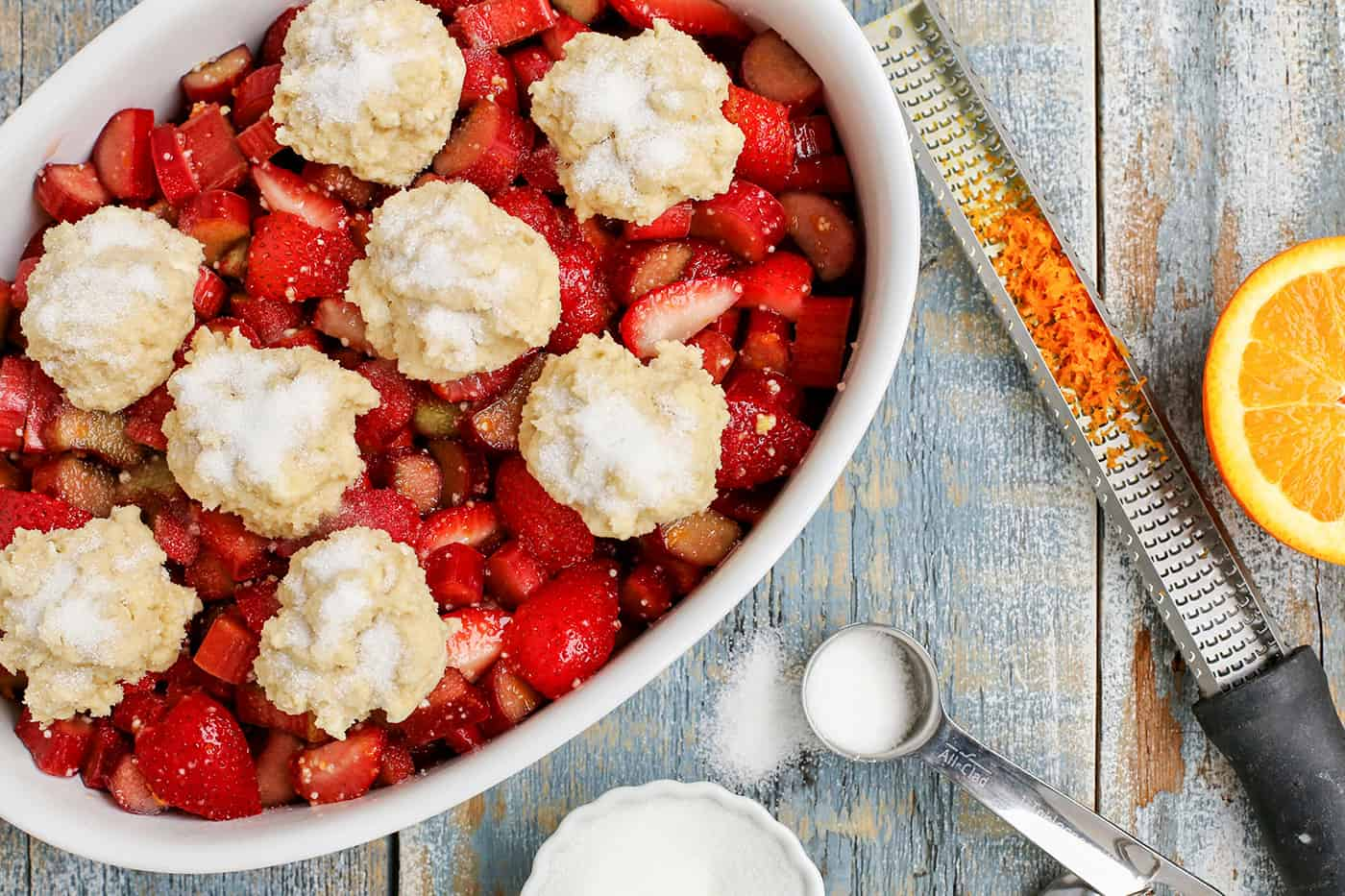 Unbaked Strawberry Rhubarb Cobbler in an oval baking dish next to ingredients