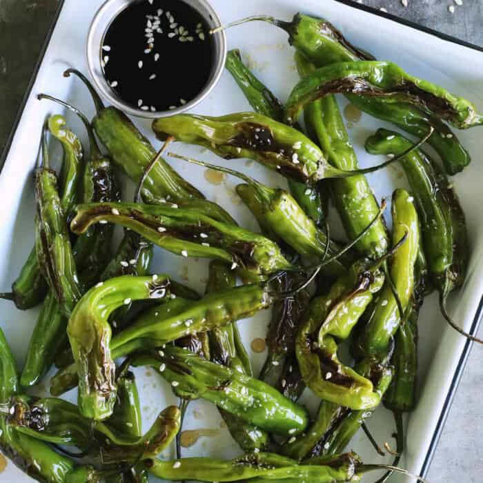 blistered shishitos on a white enamel tray with soy dipping sauce