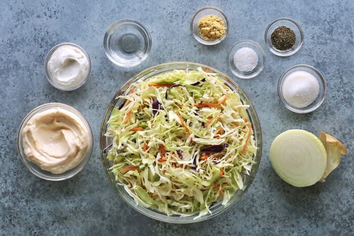 coleslaw ingredients in clear bowls: shredded cabbage, mayonnaise, sour cream, vinegar, ground mustard, salt, pepper, sugar, and half a yellow onion