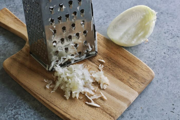 grating a yellow onion on a box grater