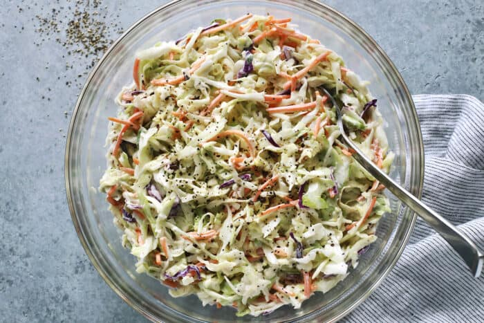 fresh shredded cabbage and carrots dressed with a mayo and sour cream based dressing, in a clear bowl