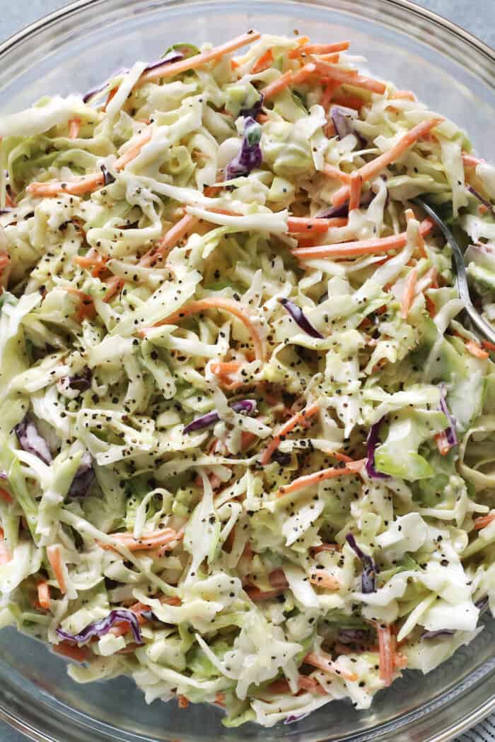 close-up photo of creamy coleslaw in a clear bowl
