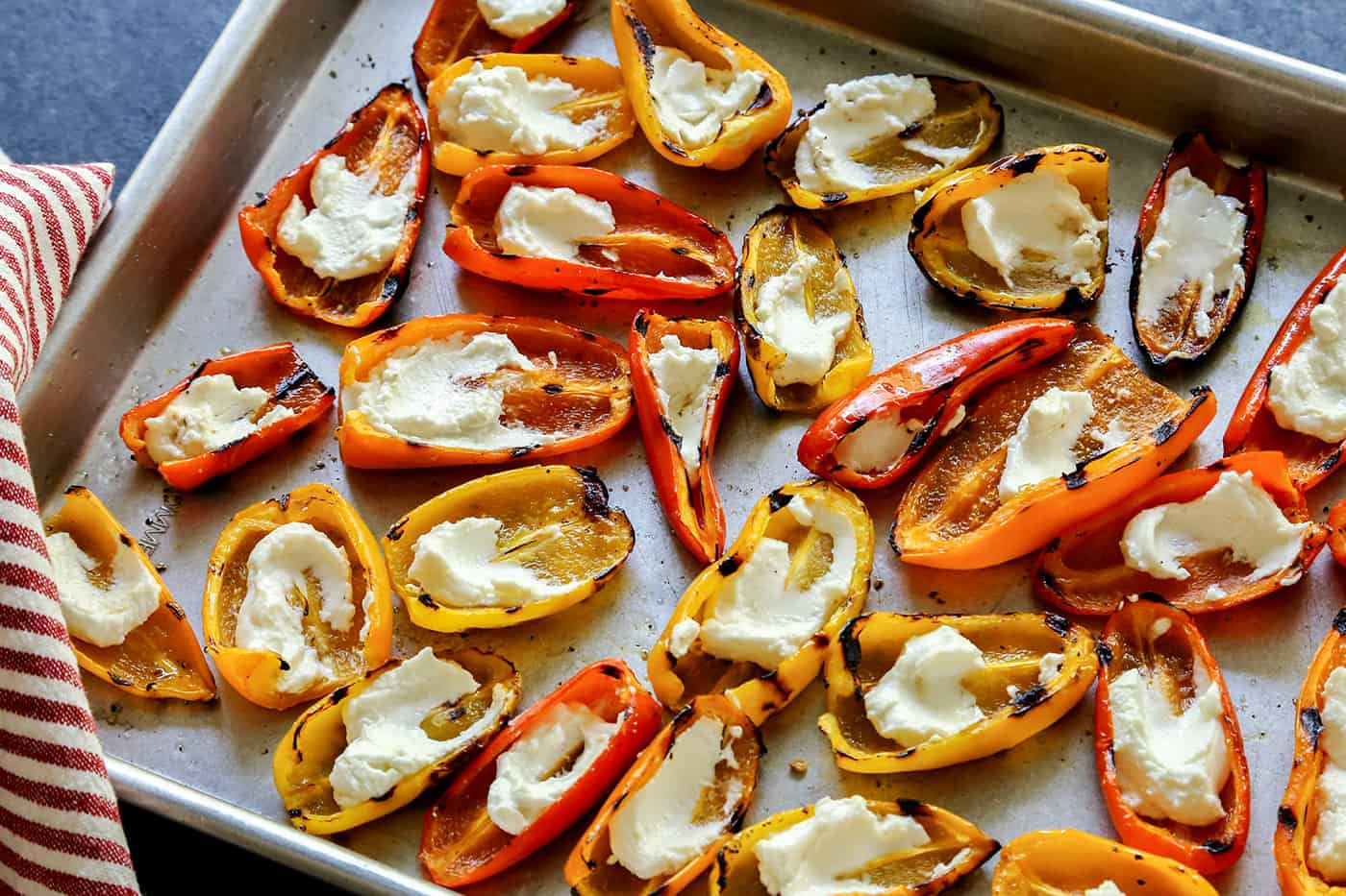 A sheet pan of Grilled Mini Sweet Peppers filled with Goat Cheese