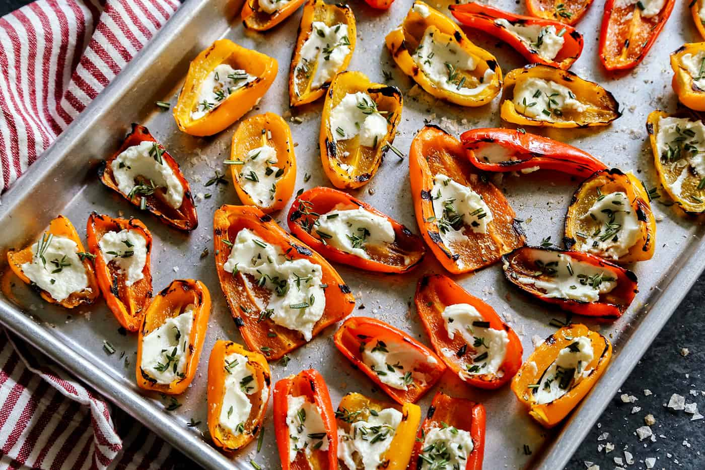 Overhead view of Grilled Mini Sweet Peppers filled with Goat Cheese on a sheet pan