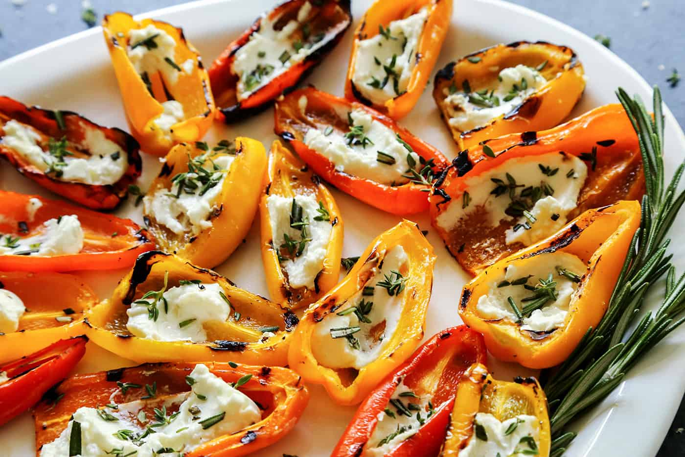 Grilled Mini Sweet Peppers filled with Goat Cheese on a white platter