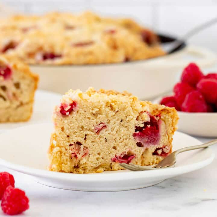 a piece of coffee cake with raspberries and rhubarb, on a white plate with a fork