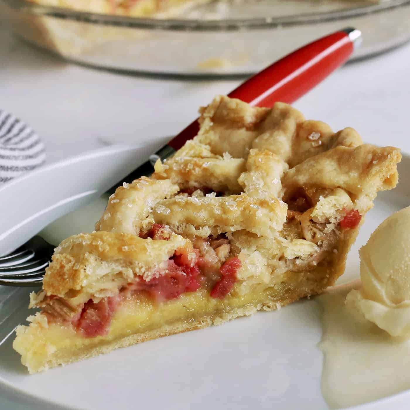 a slice of rhubarb custard pie on a white plate with a scoop of ice cream