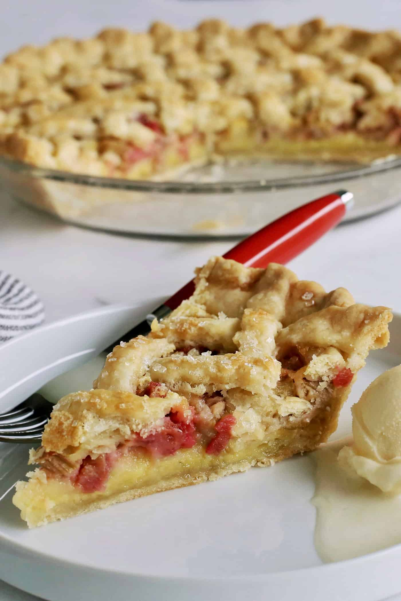 a slice of rhubarb custard pie on a white plate, with the pie plate in the background