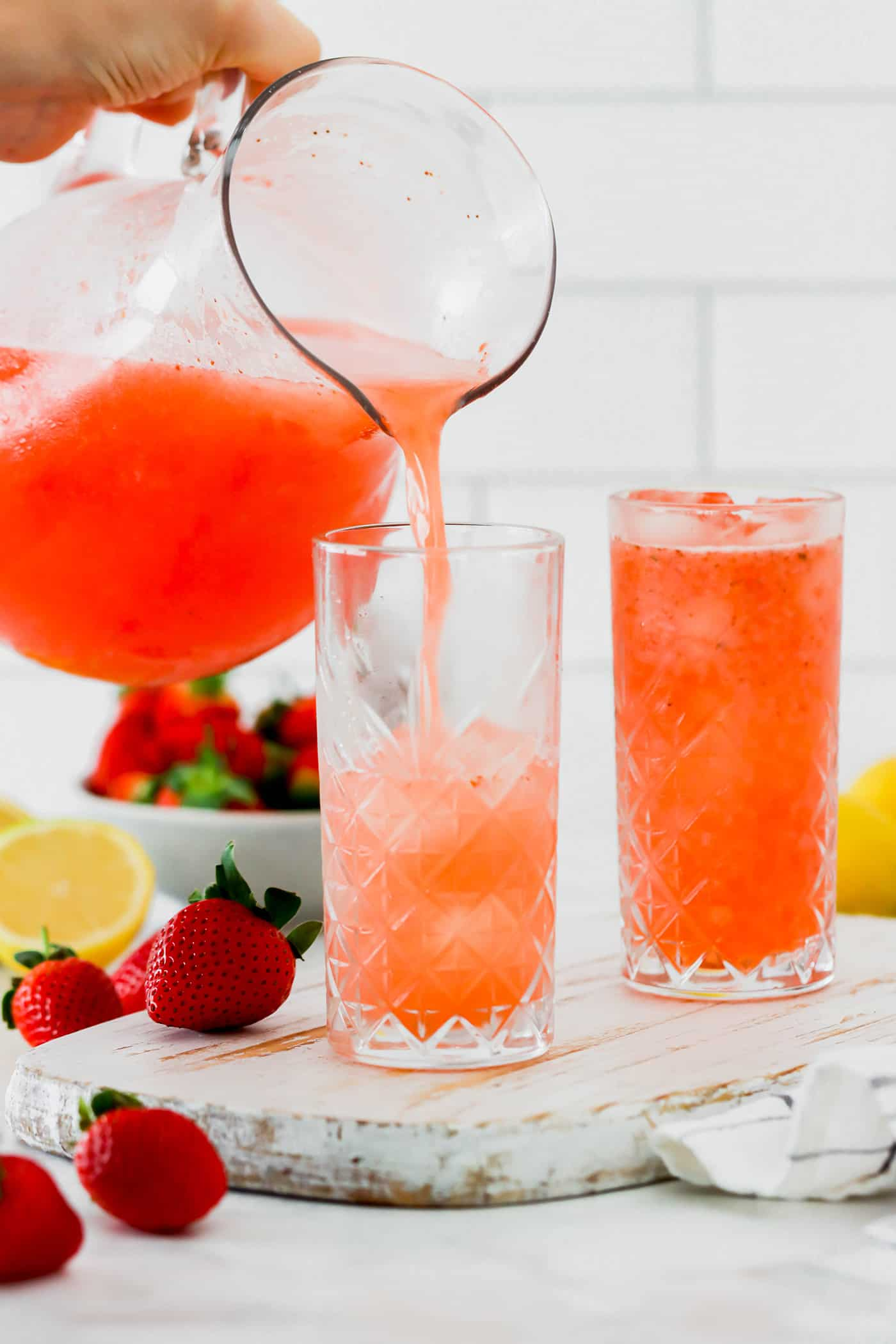 pouring strawberry lemonade from a pitcher into glasses