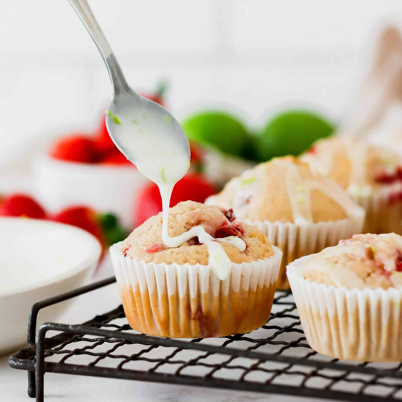 Drizzling lime glaze onto strawberry muffins