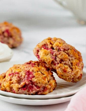 two raspberry scones on a small white plate