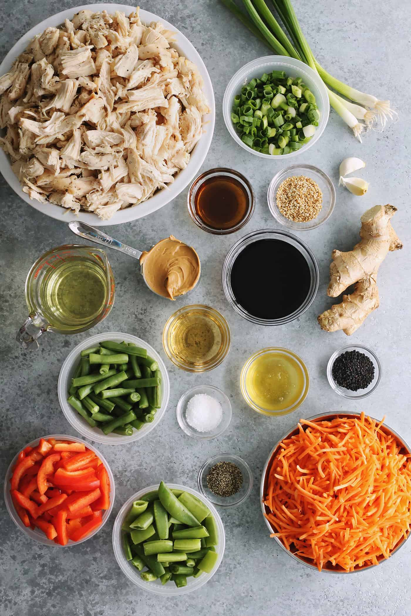 ingredients to make Chinese chicken salad, to include shredded chicken, fresh pea pods, red pepper, carrot, and green beans, plus a creamy peanut dressing