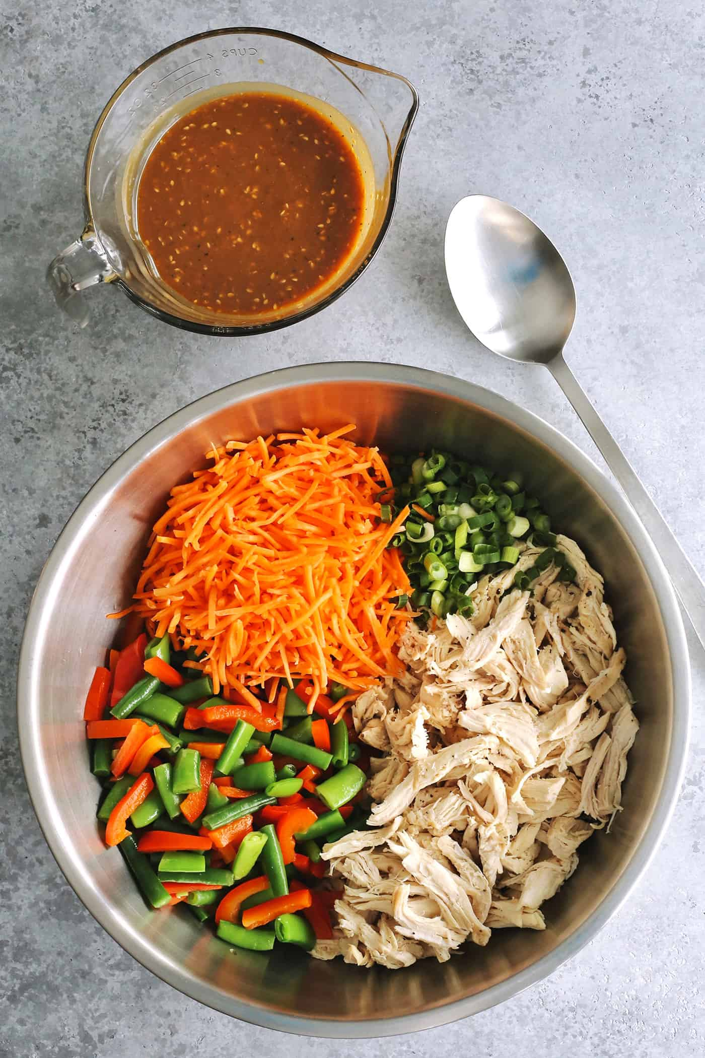 shredded chicken and cut vegetables in a large stainless steel bow, with a glass measure of peanut dressing on the side