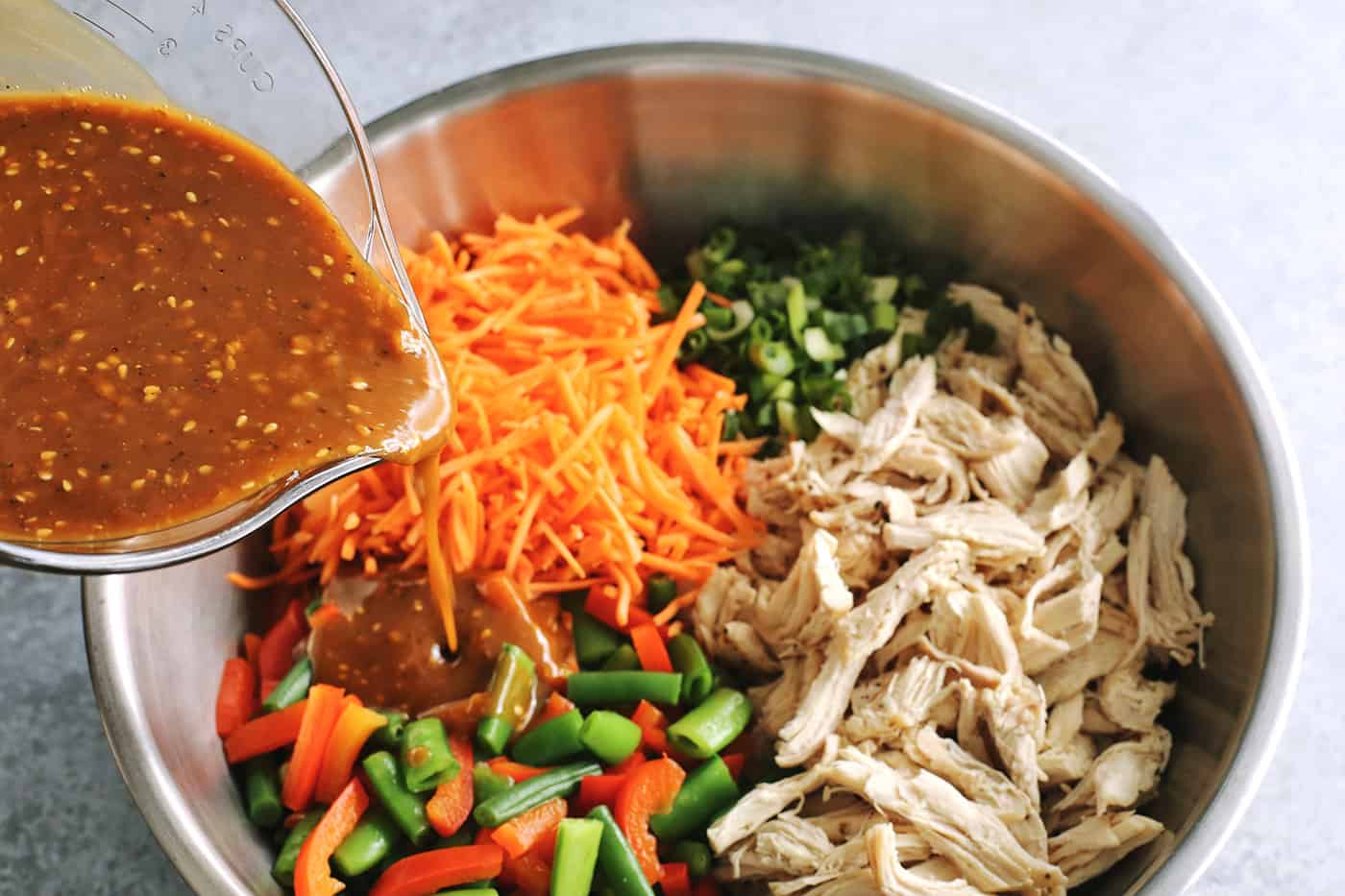 pouring creamy peanut sauce over stainless steel bowl of shredded chicken and chopped vegetables