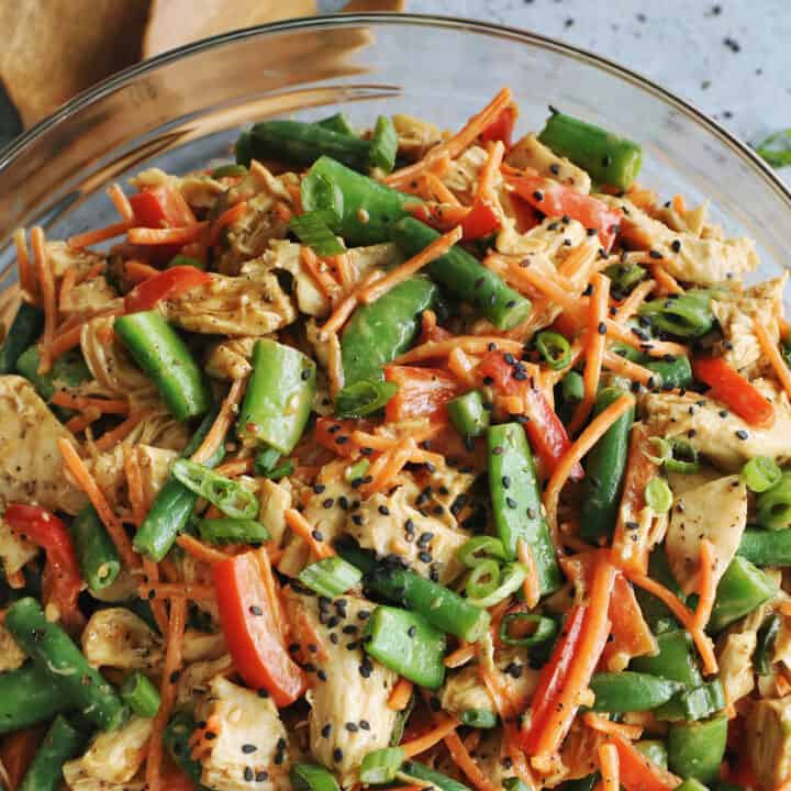 chicken salad with fresh veggies and a peanut butter dressing, in a clear serving bowl