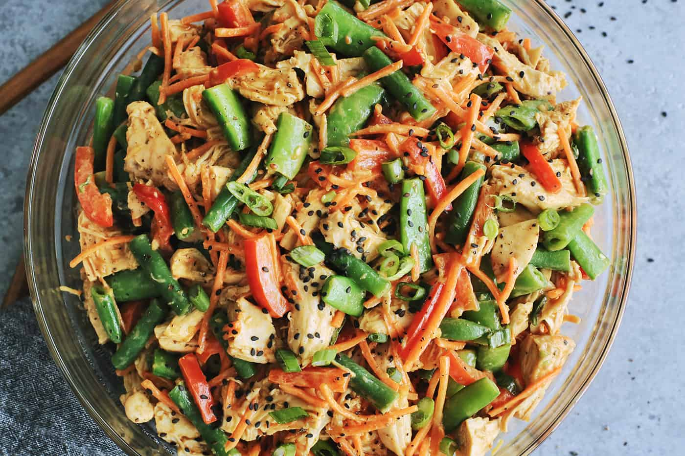 chicken salad with creamy peanut sauce in a clear bowl