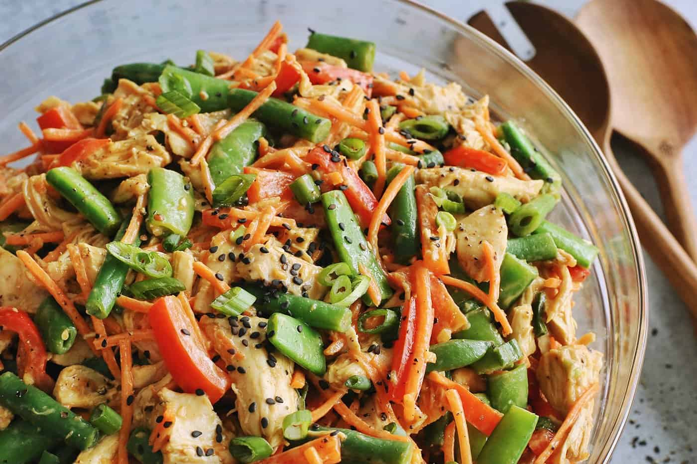 a large clear bowl of salad made of shredded chicken and chopped vegetables tossed with a peanut dressing