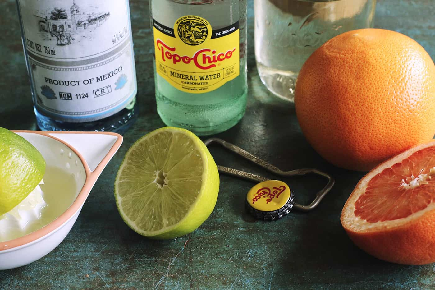fresh lime and grapefruit, bottles of tequila and mineral water, and a jar of simple syrup