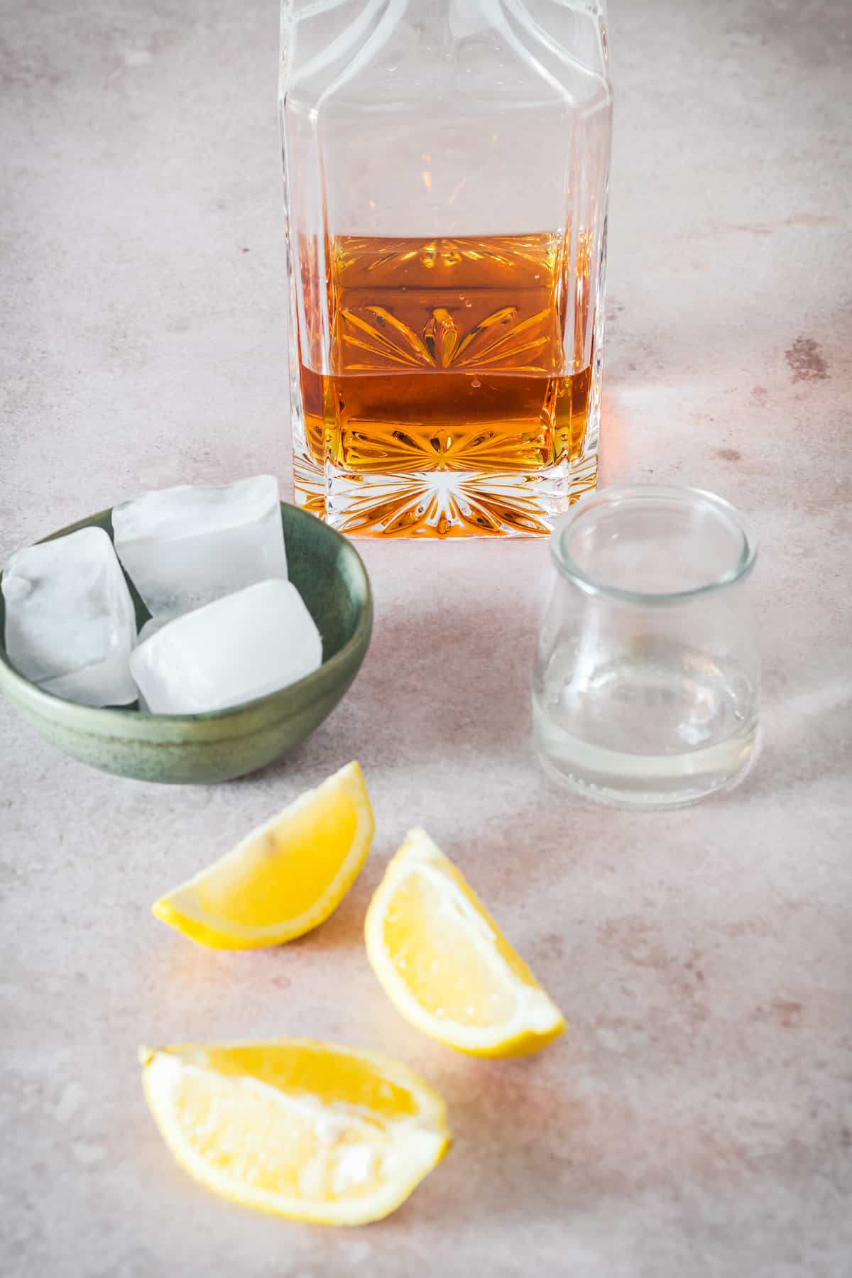 Whiskey sour ingredients - whiskey, ice, and lemon slices