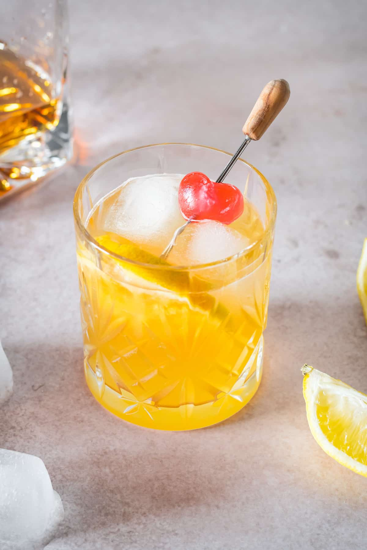 A whiskey sour garnished with a cherry and orange slice