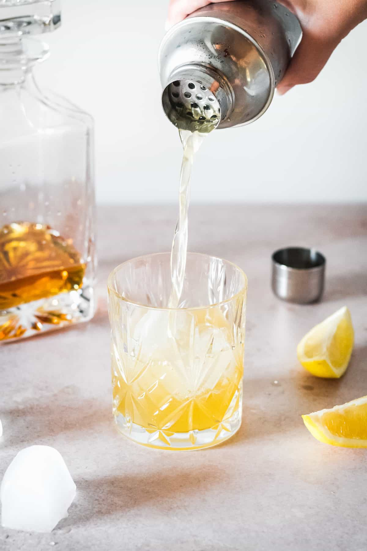 Bourbon sour being poured into a glass over ice