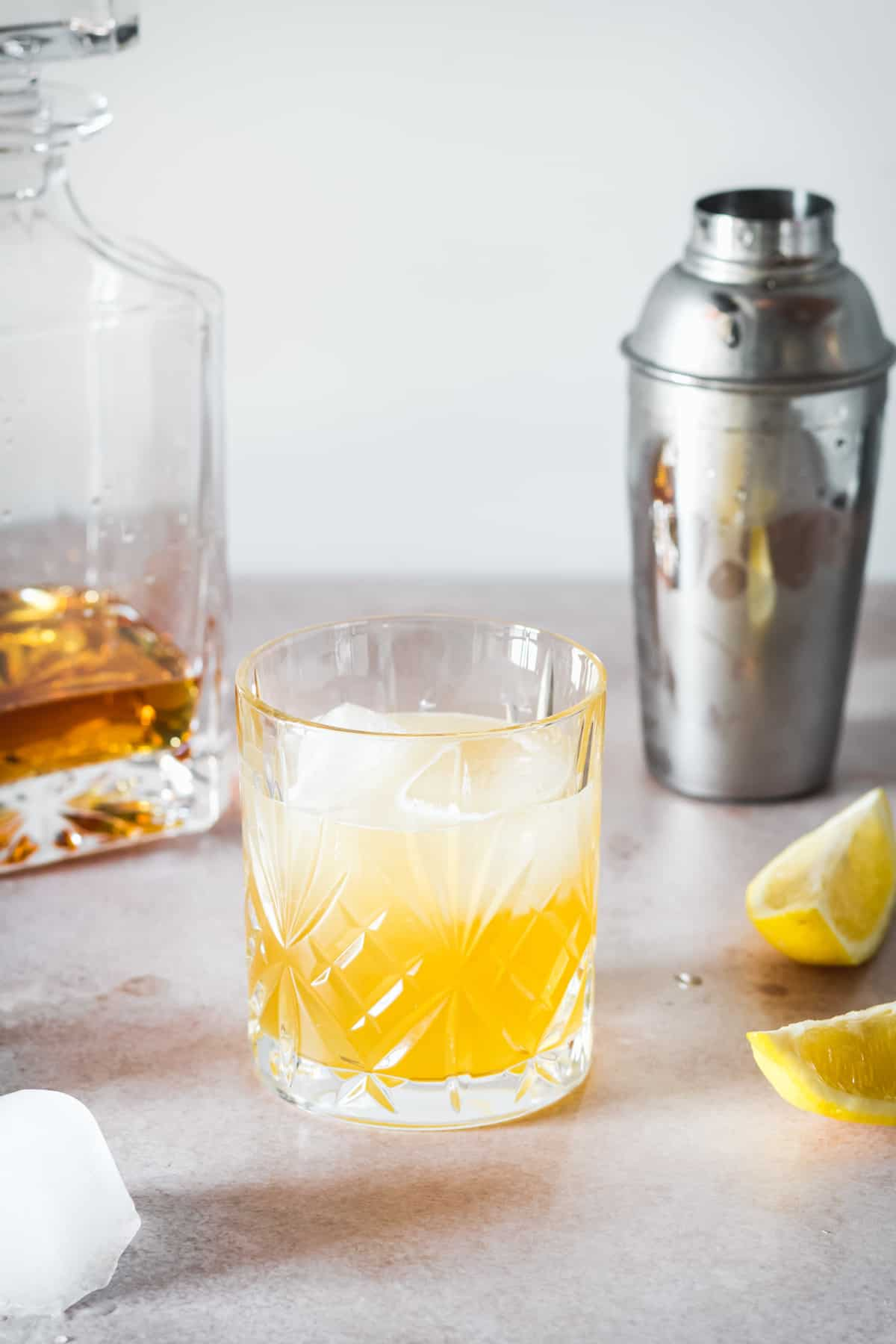 A whiskey sour over ice in front of a bottle of whiskey and a shaker