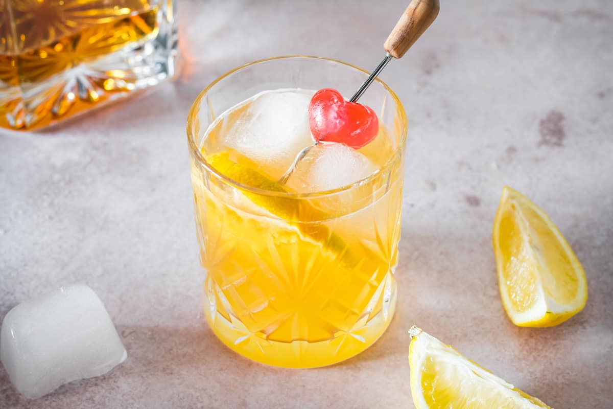 A bourbon sour garnished with a cherry and orange slice