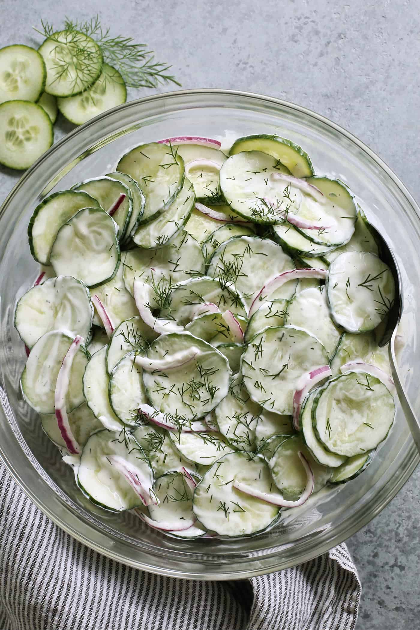 a large clear serving bowl of creamy cucumber salad