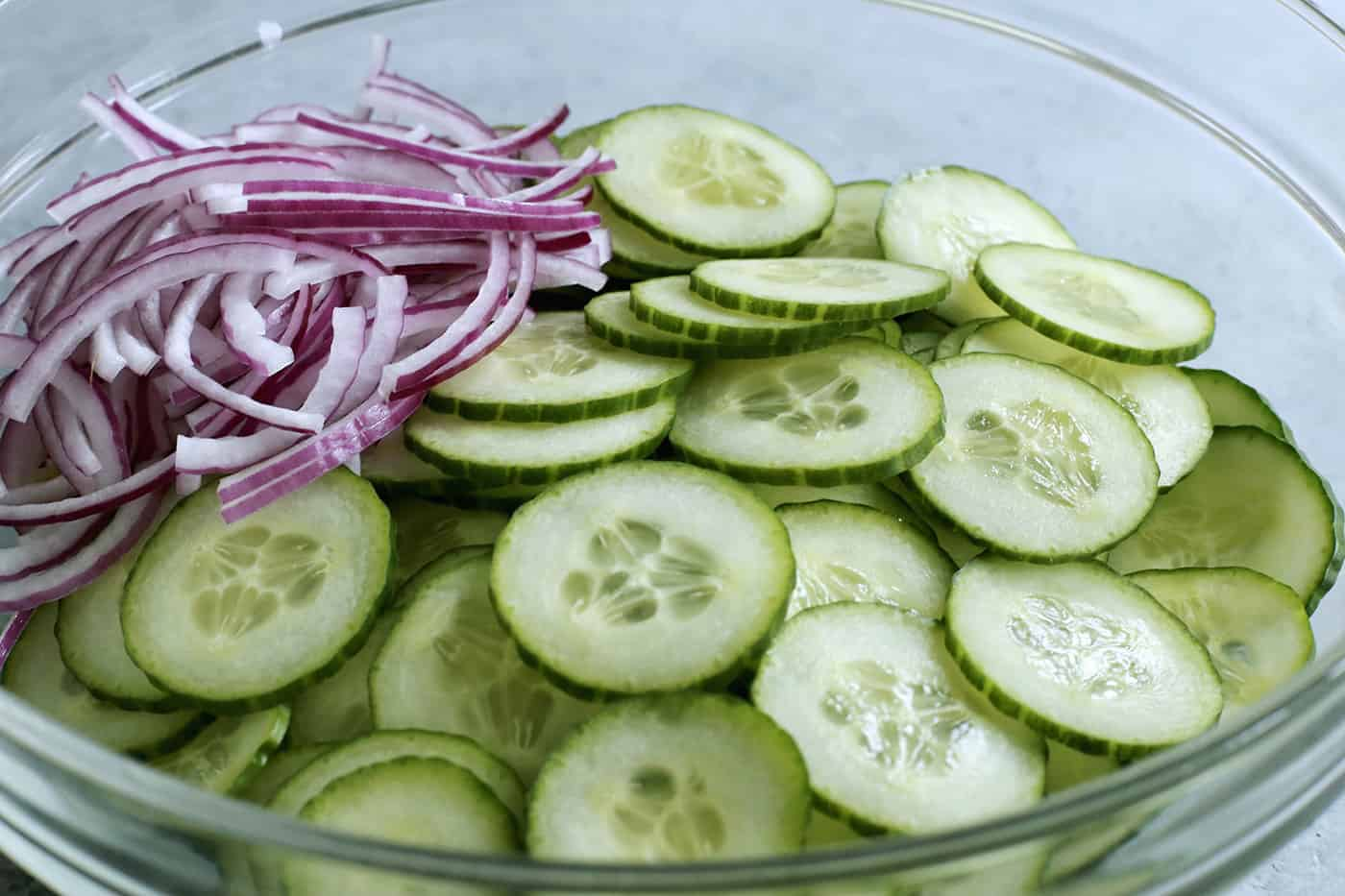 close-up photo of cucumber and red onion slices in a clear bowl