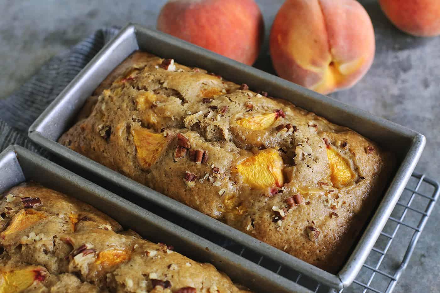 two pans of peach bread, plus a few fresh peaches