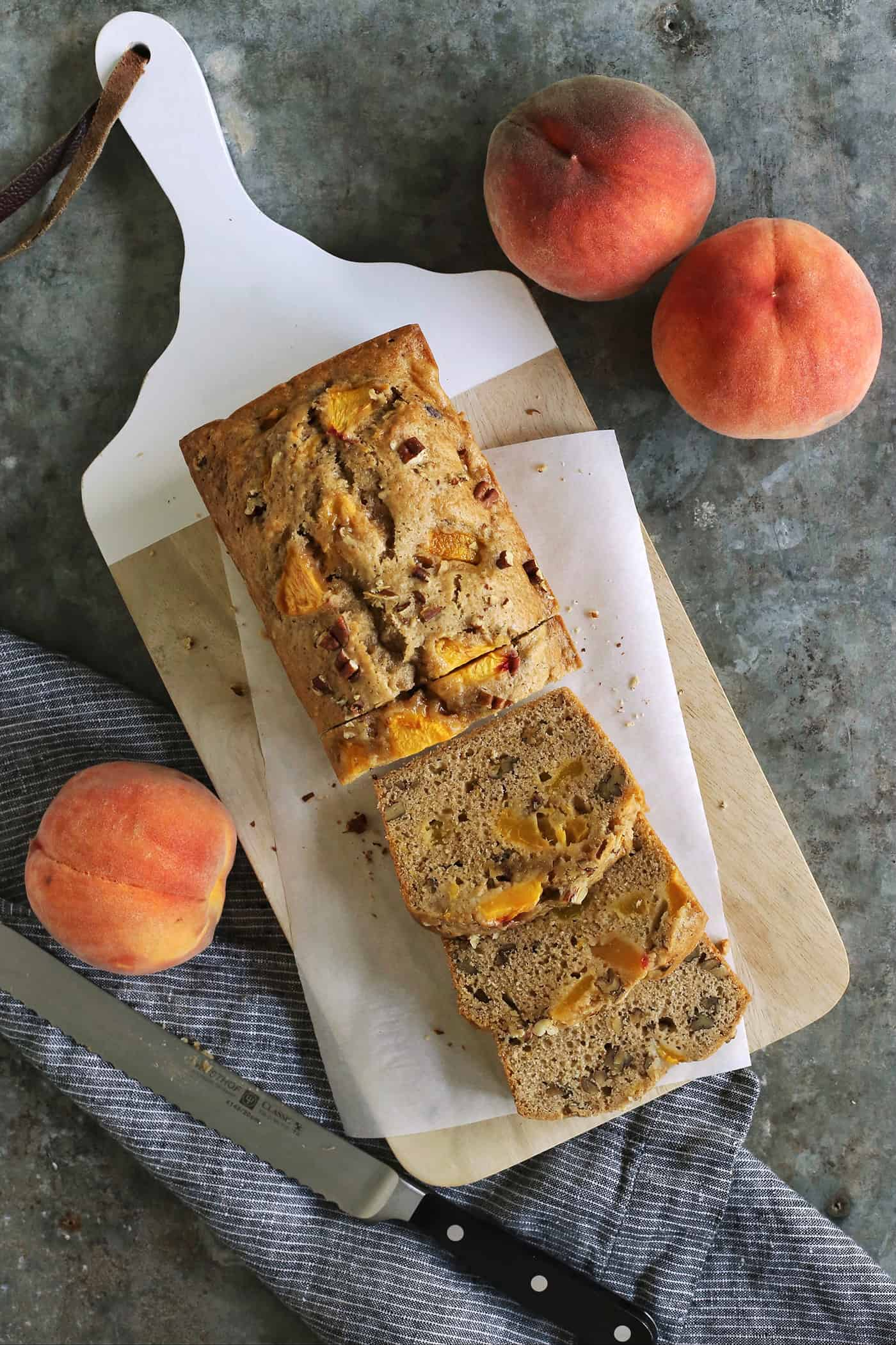 a cutting board with a loaf of peach bread that is partially sliced