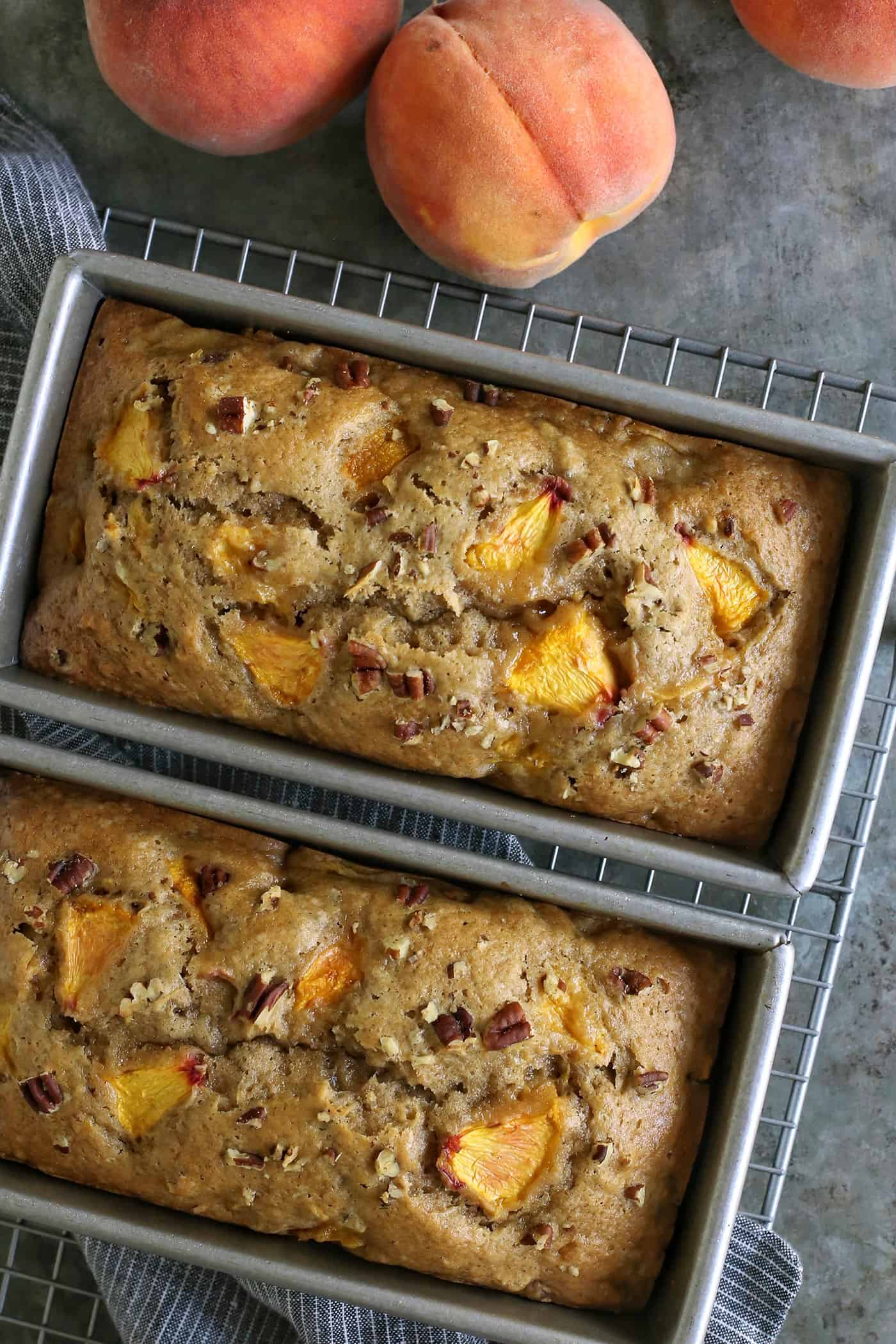 two loaves of peach bread still in the baking pans