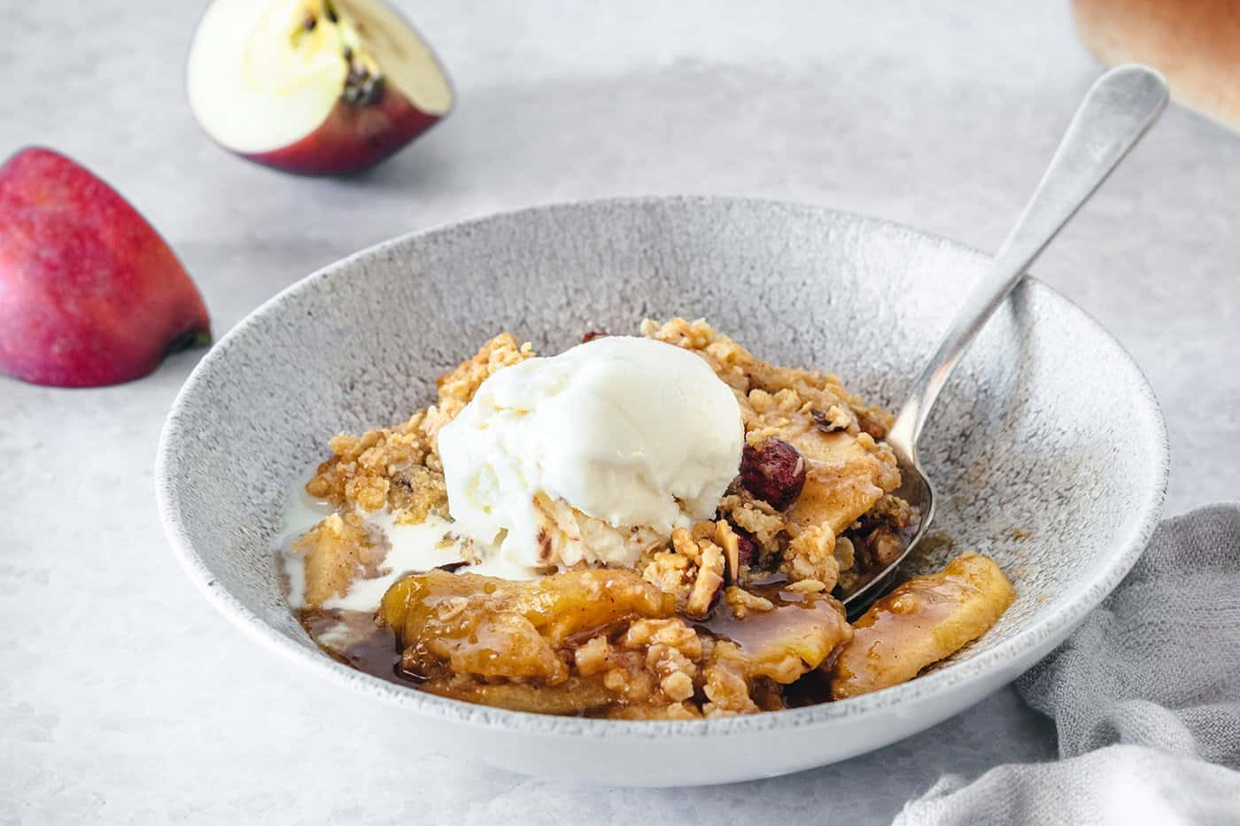 apple crisp with caramel and almond in a low wide gray bowl, plus a scoop of vanilla ice cream