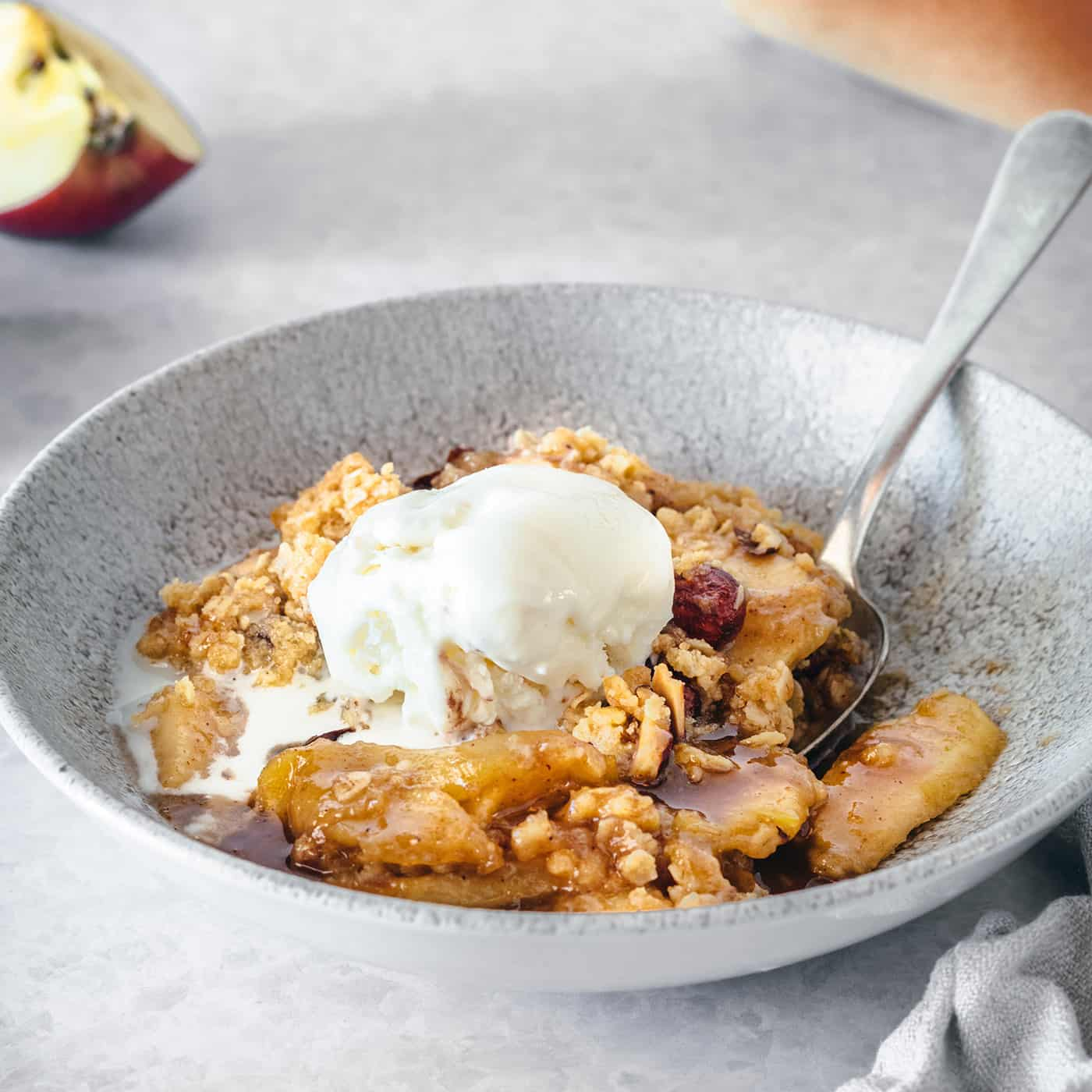 apple crisp with caramel and almonds in a low wide gray bowl, topped with a scoop of ice cream