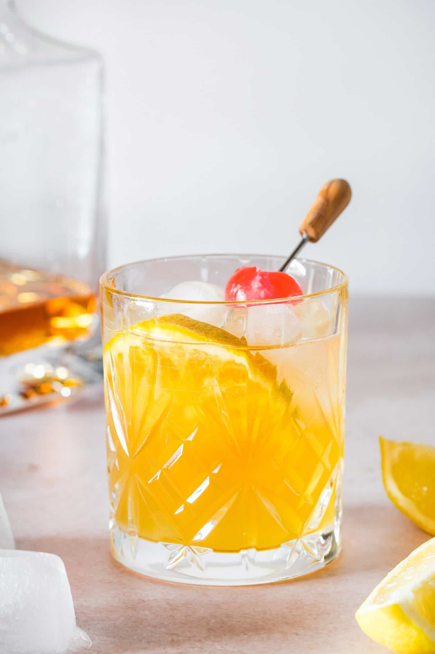 whiskey sour cocktail garnished with an orange slice and cherry