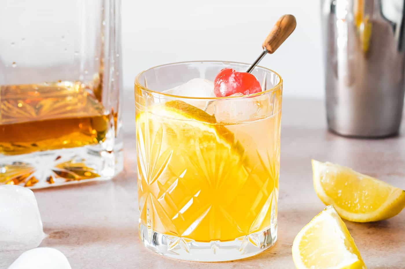 a classic whiskey sour made without egg white, garnished with an orange slice and cherry