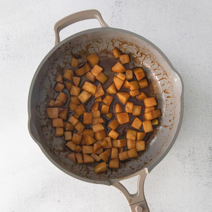 sauteeing the chopped apples in a skillet