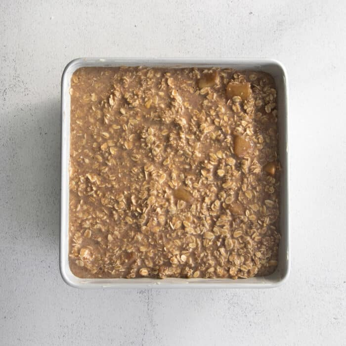 unbaked apple oatmeal in a square white baking dish