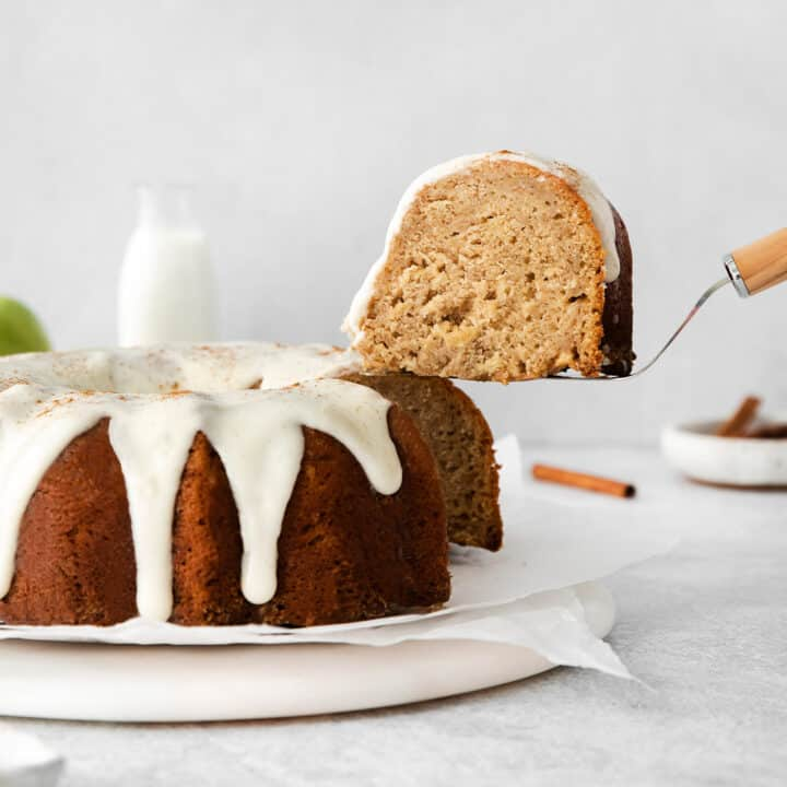 a spatula lifting a slice of cake out of the apple bundt cake