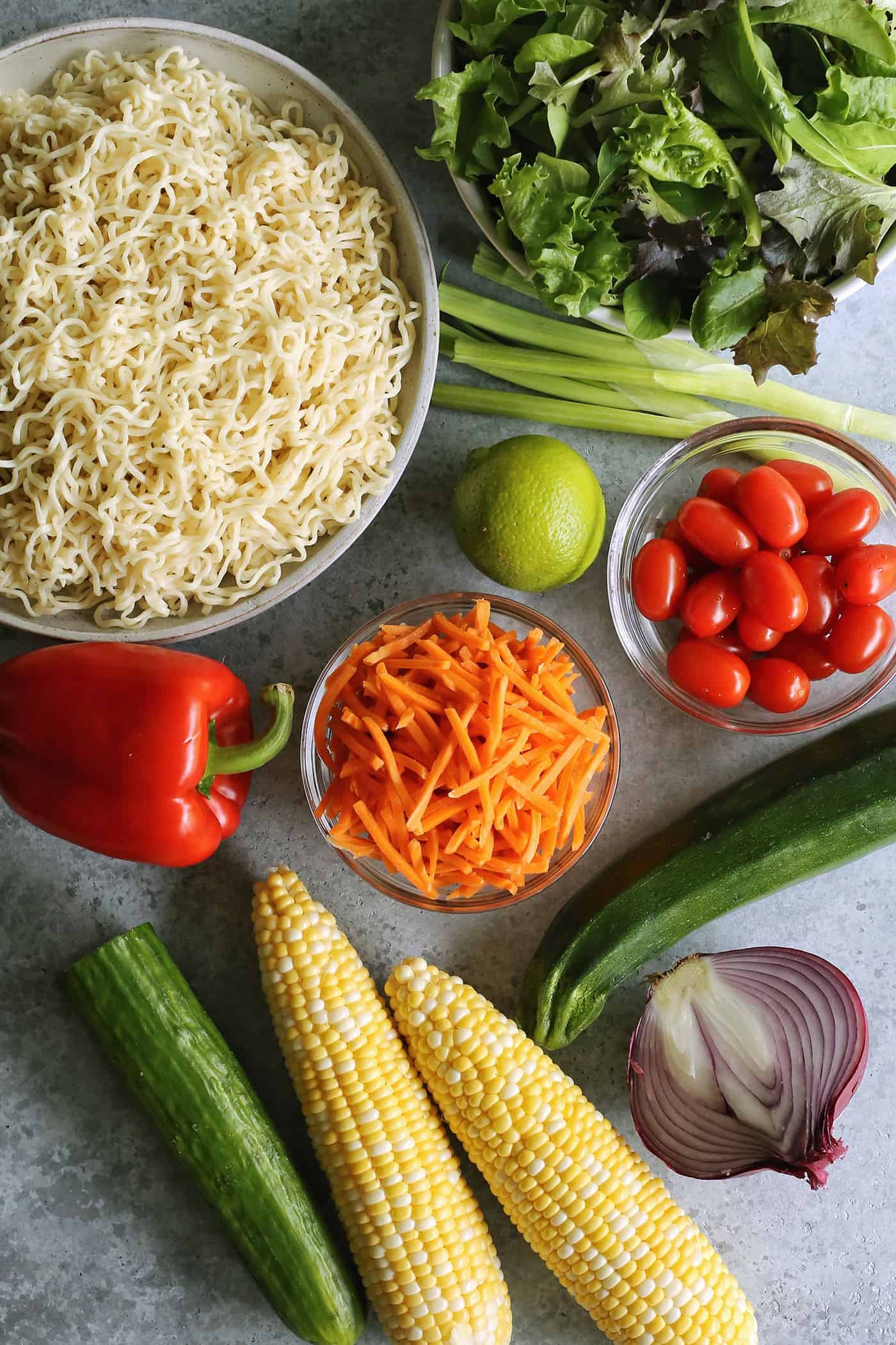 a bowl of cooked ramen noodles, plus fresh lettuce, green onion, red onion, tomatoes, lime, carrots, zucchini, sweetcorn, cucumber, and red pepper