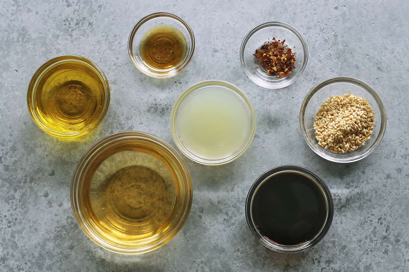ingredients to make the salad dressing, in separate clear bowls